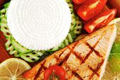 grilled salmon and greek cheese on wooden plate