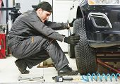car mechanic screwing or unscrewing car wheel of lifted automobile by pneumatic wrench at repair service station