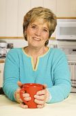Happy Woman Holds A Coffee Mug In Her Kitchen