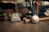 picture of attic  - Group of vintage objects on attic hardwood floor including old toys phone and sports items - JPG