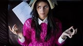 Funny looking brunette woman student trying to study in her room. Funny process of studying for exam