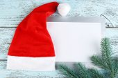 Santa red hat with fir-tree branch and card on color wooden background