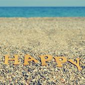 wooden letters forming the word happy on a shingle beach, with a filter effect