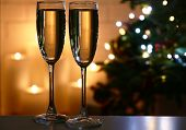 Champagne glasses on table, on fir-tree and fireplace background