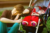 Sleeping young mother and her baby daughter in a stroller