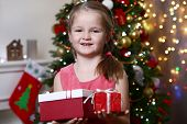 Little girl holding present boxes near Christmas tree on light background