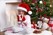 Little girl in Santa hat and mittens taking cup sitting near fir tree on fur carpet and wooden floor, on fireplace with candles background