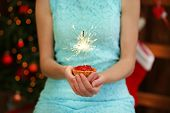 Woman holding cake with sparkler, on shiny background