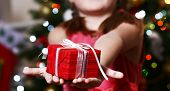 Little girl holding present box near Christmas tree on light background