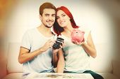 Loving couple sitting in sofa with piggy bank in room