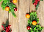 Fresh ripe mandarins, Christmas decorations and fir tree bud on wooden background