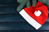 Santa red hat with branch of fir-tree on color wooden background