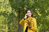 Happy beautiful woman calling by phone in autumn street