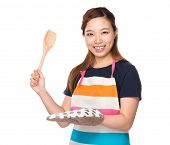 Asian Housewife hold with wooden ladle and oven gloves
