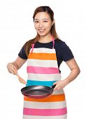 Housewife cooking with fried pan and wooden ladle