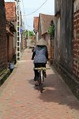 Unidentified Vietnamese woman cycling on a country road