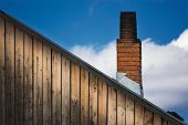 stock photo of gable-roof  - The old brick chimney on the roof in the countryside - JPG
