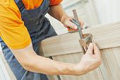 Close-up carpenter hands with doorlock during lock process installation into wood door