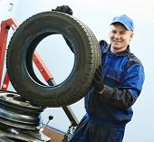 Auto repairman portrait with automobile car wheel tyre at during tire replacing on fitting machine