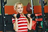 Young woman training exercises with barbells in fitness club gym