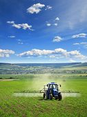 foto of tractor  - Farming Tractor Plowing And Spraying On Field - JPG