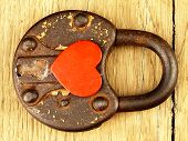 Rusty Padlock And Heart On A Wooden Background.