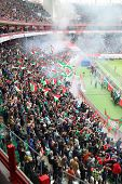 MOSCOW, RUSSIA - MAR 30, 2014: Fans launching smoke flare and waving flags at the stadium Locomotive