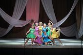 MOSCOW, RUSSIA - MAR 18, 2014: Dance group of eight girls in colorful costumes on stage in Palace of Children and Youth HLW
