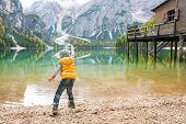image of south tyrol  - Child throwing stones on lake braies in south tyrol italy - JPG