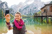 Happy Young Woman Making Selfie On Lake Braies In South Tyrol, Italy