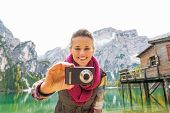 Portrait Of Happy Young Woman Taking Photo On Lake Braies In South Tyrol, Italy