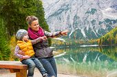 Portrait Of Happy Mother And Baby On Lake Braies In South Tyrol, Italy Pointing On Copy Space