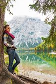 pic of south tyrol  - Full length portrait of young woman standing near tree on lake braies in south tyrol italy - JPG