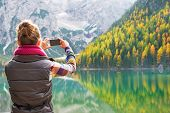 Young Woman Taking Photo On Lake Braies In South Tyrol, Italy. Rear View