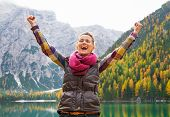 stock photo of south tyrol  - Happy young woman on lake braies in south tyrol italy rejoicing - JPG
