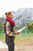stock photo of south tyrol  - Happy young woman with map on lake braies in south tyrol italy - JPG