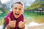 picture of south tyrol  - Portrait of happy young woman on lake braies in south tyrol italy showing thumbs up - JPG