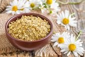 picture of chamomile  - Dry chamomile and fresh flowers on a wooden table - JPG