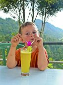 Boy Drinks A Fruity Lemon Juice In A Restaurant With View To The Jungle