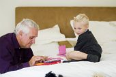 grandfather and grandson playing on bed