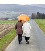 Women In Rain Under An Umbrella In Rural Landscape