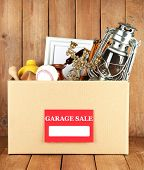 Box of unwanted stuff ready for a garage sale on wooden background