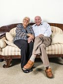 Senior  Couple In Love Sitting On A Sofa