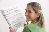 Attractive Young Woman Holding Sheet Music And Smiling