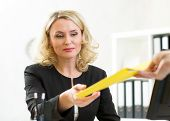 middle-aged businesswoman giving paper to colleague