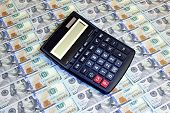 Calculator On Background Of Hundred Dollar Bills