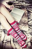 stock photo of floor heating  - female legs in Christmas socks with a book and a cup of coffee - JPG