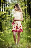 Young beautiful girl in a yellow dress in the woods. Portrait of romantic woman in fairy forest