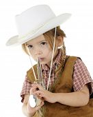 Closeup of an adorable preschool cowgirl pretending to blow smoke of the end of the toy gun she hold.  On a white background.