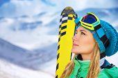 Closeup portrait of beautiful skier girl wearing mask and holding ski, enjoying winter holidays in Europe